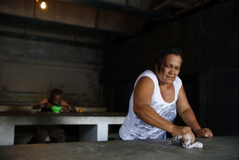 Fernanda Bolivar, 54, cleans a table after have been served lunch at the Mother Teresa of Calcutta eating center in Caracas